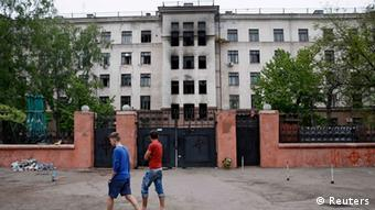 People pass by the burnt trade union building, the site of recent street battles between pro-Russian and pro-Ukrainian supporters (photo: REUTERS/Gleb Garanich)