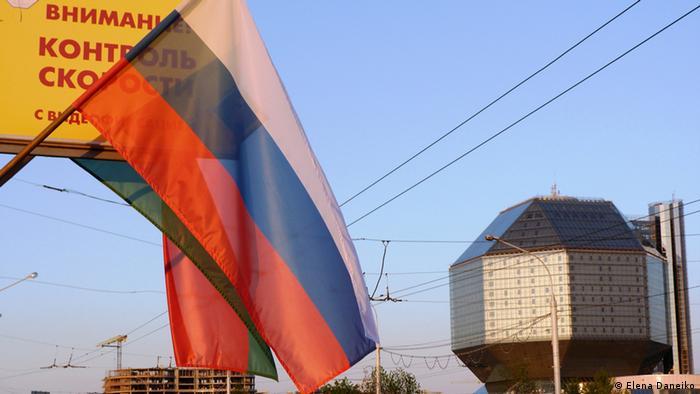Российский флаг на фоне национального белорусского флага на улице в Минске