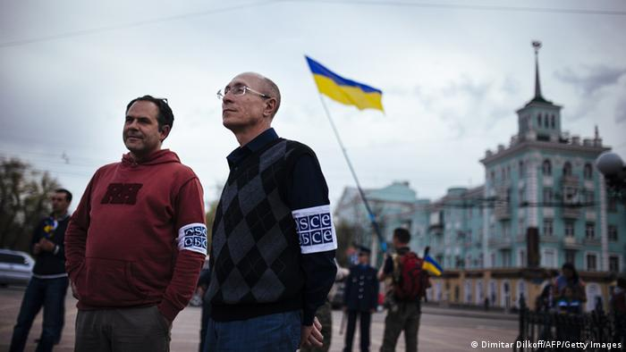 Two OSCE monitors watch during a pro-Ukrainian rally in the eastern Ukrainian city of Lugansk on April 19, 2014. Russia was under US pressure to convince pro-Moscow rebels in Ukraine to cease occupying eastern towns, after Washington warned the situation in the former Soviet republic was in a 'pivotal period'. AFP PHOTO / DIMITAR DILKOFF (Photo credit should read DIMITAR DILKOFF/AFP/Getty Images)