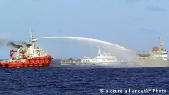 A Chinese ship, left, shoots water cannon at a Vietnamese vessel, right, while a Chinese Coast Guard ship, center, sails alongside in the South China Sea, off Vietnam's coast, Wednesday, May 7, 2014 (AP Photo/Vietnam Coast Guard)