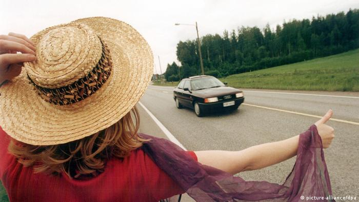 A woman holding her finger out on the sreet to catch a ride