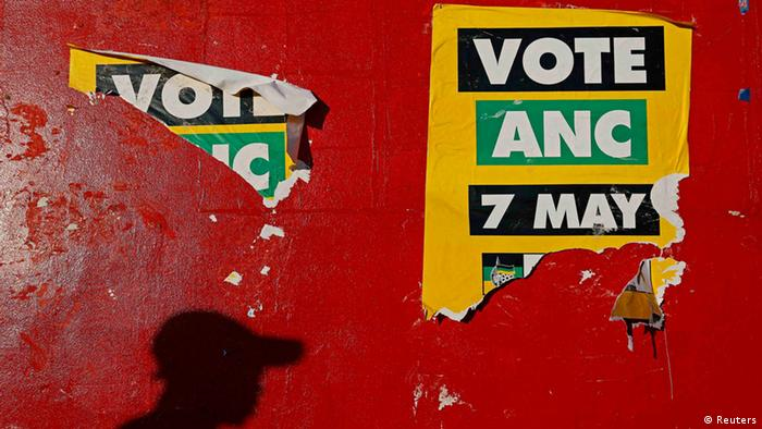 A shadow of a man walking past ripped ANC posters on a red wall