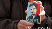 A demonstrator holds a card depicting fugitive US intelligence leaker Edward Snowden during a demonstration in favor of an appearance by Snowden as a witness in German NSA hearings held in the German Bundestag, or lower house of parliament, outside the Reichstag building in Berlin on May 8, 2014. Lawmakers from the opposition Greens and far-left Linke parties had demanded that the parliamentary panel probing mass surveillance by the NSA seek testimony from Snowden, the former contractor with the US National Security Agency (NSA) now living in Moscow. AFP PHOTO / ADAM BERRY (Photo credit should read ADAM BERRY/AFP/Getty Images)