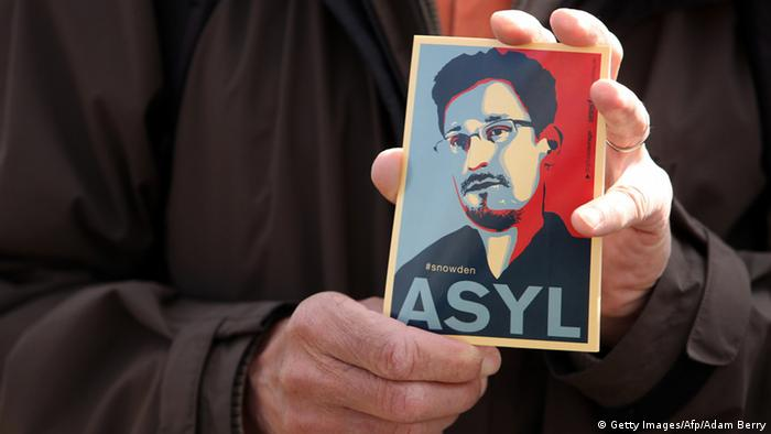 A demonstrator holds a card depicting fugitive US intelligence leaker Edward Snowden. (Photo: ADAM BERRY/AFP/Getty Images)