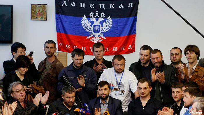 A group of men, mostly in black clothing, in front of a black, blue and red separatist flag