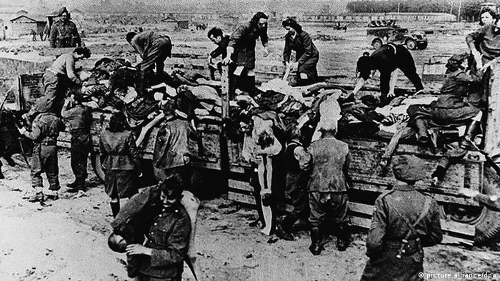 Бывшие надзиратели и охранники концлагеря убирают тела умерших узников под охраной британских солдат