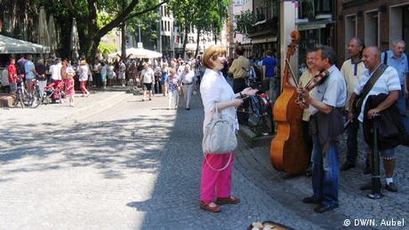 Bild von einer Straße der Düsseldorfer Altstadt, auf der Straßenmusiker spielen.
