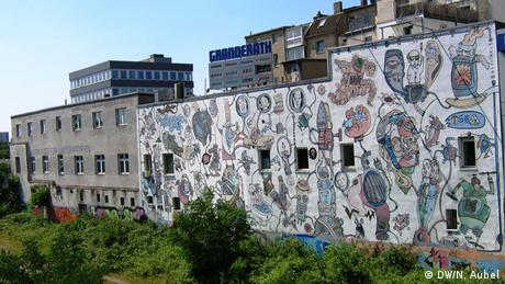 Bild aus einem Zug durch Düsseldorf mit Blick auf eine bemalte Häuserwand.