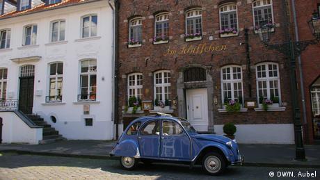 Bild von alten Häusern mit einem blauen Oldtimer davor im Stadtteil Kaiserswerth.