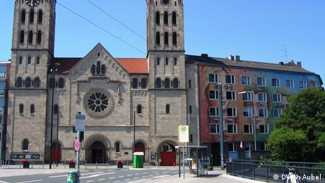 Bild von der St. Elisabeth Kirche und der angrenzenden bemalten Häuserfront.