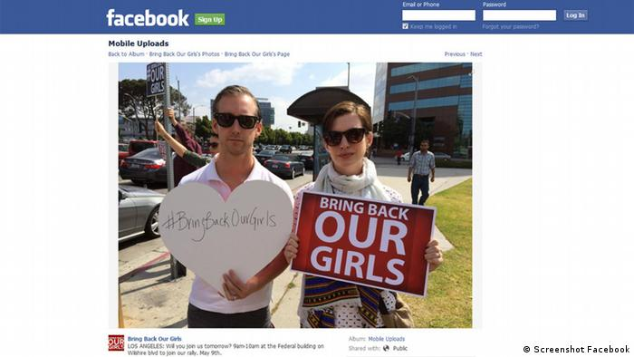 Anne Hathaway and Alan Schulman hold signs reading bring back our girs 