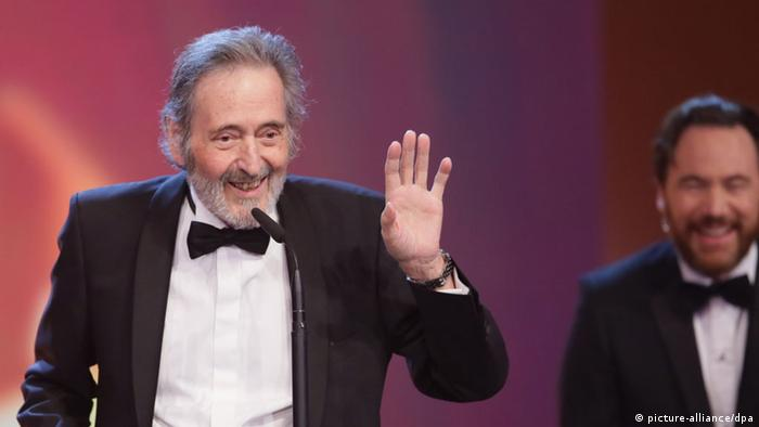 Helmut Dietl raises his hand onstage (picture-alliance/dpa)