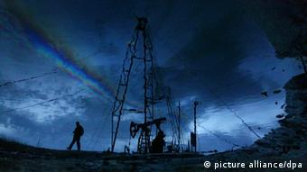 A man is passes an oil derrick near Baku