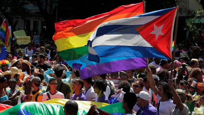 Multidão em parada em Havana exibe bandeiras de Cuba e bandeiras arco-íris, símbolo do movimento gay