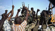 Sudan People's Liberation Army (SPLA) soldiers wave their AK-47s in the air as they celebrate alongside Internally Displaced People (IDP) outside the United Nations Mission in the Republic of South Sudan (UNMISS) base in Malakal after the SPLA claimed it had recaptured the town from rebels on March 19, 2014. The northeastern town of Malakal, capital of oil-producing Upper Nile state, has been one of the hardest fought battlegrounds in the conflict, in which thousands have been killed. South Sudan's government has been at war with rebel groups since December 15, when a clash between troops loyal to President Salva Kiir and those loyal to sacked vice president Riek Machar snowballed into full-scale fighting across the world's newest nation. AFP PHOTO / IVAN LIEMAN (Photo credit should read Ivan Lieman/AFP/Getty Images)