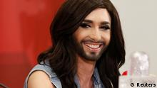 Austria's Conchita Wurst (C) arrives with her trophy at Vienna's airport May 11, 2014. Wurst, popularly known as the bearded lady, won the 59th annual Eurovision Song Contest on Saturday with the James Bond-theme-like ballad Rise Like a Phoenix, before a global TV audience of about 180 million people in 45 countries. REUTERS/Leonhard Foeger (AUSTRIA - Tags: ENTERTAINMENT)