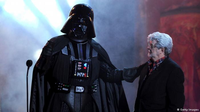 George Lucas on his 70th birthday standing next to Darth Vader