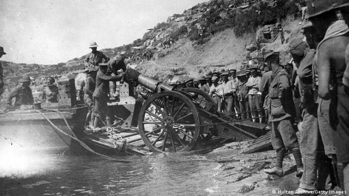 Gallipoli in 1915: A black and white photo of a canon being pushed onto a beach, surrounded by soldiers. (Hulton Archive/Getty Images)