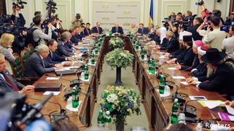 People sit around a long table during talks in Kyiv, Ukraine (Photo: Andrew Kravchenko/REUTERS)