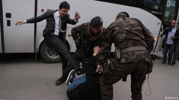 A Turkish politician kicks a protestor