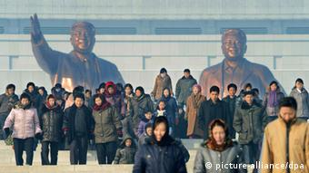 People near bronze statues of the late former North Korean leaders Kim Il Sung (L) and Kim Jong Il