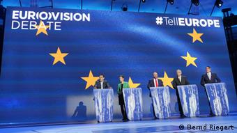 Five People stand in behind their speaker's desks and infront of a blue wall with yeallow stars (Foto: Bernd Riegert/DW)