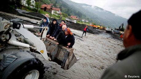 People are carried by a front loader as they evacuate from their flooded houses in Topcic Polje, near Zepce Photo: REUTERS/Dado Ruvic