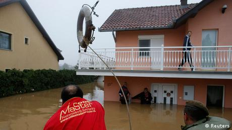 A man throws a life buoy towards people waiting to be evacuated from a flooded house in the town of Obrenovac Photo: REUTERS/Marko Djurica