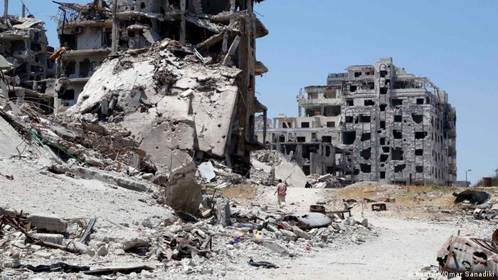 Men walk past damaged buildings in Homs, Syria in May 2014 (Reuters/Omar Sanadiki)