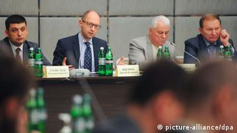 Politicians, among them Arseniy Yatsenyuk, sit at a table