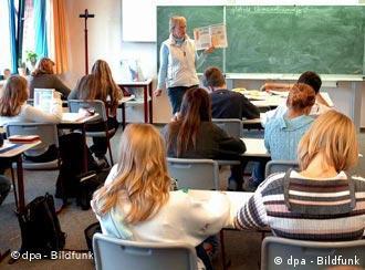 Lehrehrin vor Schülern dun Schülerinnen in Klassenraum (Quelle: dpa)
