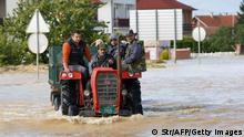 Bosnian men ride a tractor in a flooded street in the Eastern-Bosnian town of Bijeljina on May 17, 2014. The heaviest rains in more than a century have sparked floods across Bosnia and Serbia, claiming at least 30 lives and leading to the evacuation so far of more than 16,000 from flooded villages, officials said Saturday. AFP PHOTO / STRINGER (Photo credit should read STR/AFP/Getty Images)