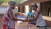 A election official, right, marks a woman's finger, as proof that she cast her ballot at a polling station in Bissau, Guinea-Bissau, Sunday, May 18, 2014. People in the small country of Guinea-Bissau began casting their ballots in a presidential run-off election on Sunday. (AP Photo/Youssouf Bah)