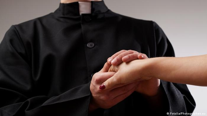 A symbolic picture of a priest holding a female's hand.