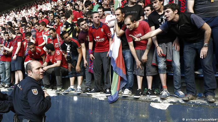 Police officers and Red Cross members help injured supporters in a torrent of people during their Spanish Liga Primera Division soccer match between Osasuna and Betis played at the El Sadar stadium, in Pamplona, northern Spain, 18 May 2014.