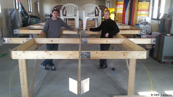 A picture of the two adventurers standing in front of the frame of the boat they are making in the boathouse.