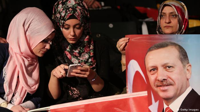 Female supporters hold a placard of Turkish Prime Minister Erdogan