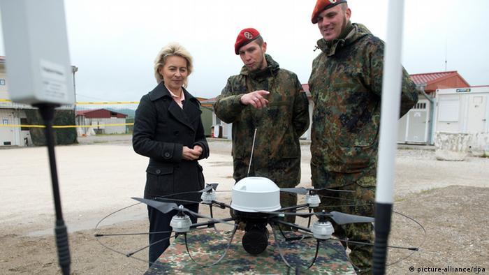 Ursula von der Leyen with two soldiers remote-controlling a drone. (Photo: Maurizio Gambarini/dpa)
