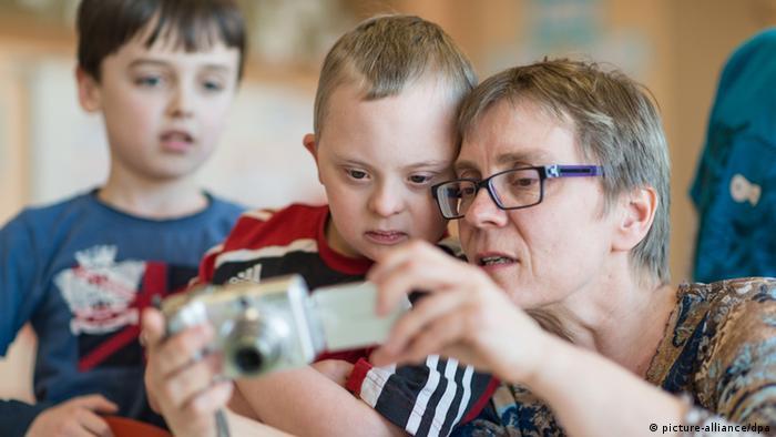Henri Erhardt (Mitte), ein Kind mit Down-Syndrom, das aufs Gymnasium gehen soll, spielt mit seiner Mutter (Foto: dpa)