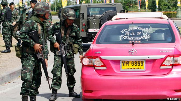 Soldiers approach a taxi in Bangkok