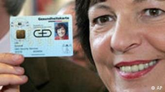 primer plano de la ministra de sanidad sujetando con la mano una tarjeta sanitaria