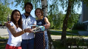 Nirina Andriamahazo aus Madagaskar, Anchel Alfaro aus Peru und Olga Dragunowa aus Russland (von links) verteilen Info-Flyer auf dem Saarbrücker Unicampus (Foto: DW/Herms)