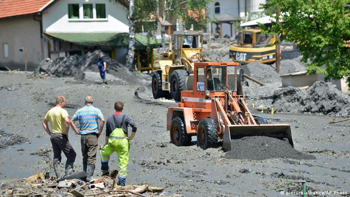 three men stand next to a dredger in muddy street (Foto: Sulejman Omerbasic/AP Photo)