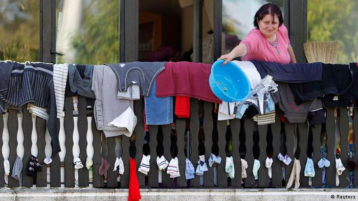 A woman throws away water as she dries clothes during heavy floods