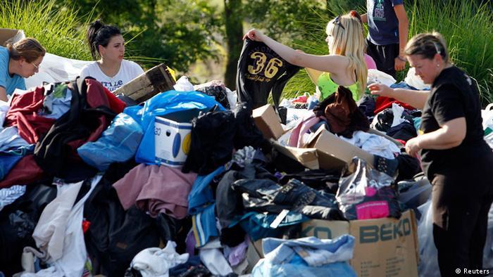 People look for clothes in a pile of donated clothes (Foto: Srdjan Zivulovic/REUTERS)
