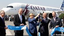 German Chancellor Angela Merkel and Turkey's Transport, Maritime Affairs and Communications Minister Lutfi Elvan (2R) hold the scissors after cutting the ribbon in front of an Airbus A350 plane during the ceremony opening the ILA Berlin Air Show in Selchow near Schoenefeld south of Berlin May 20, 2014. The ILA runs from May 20 till 25. REUTERS/Tobias Schwarz (GERMANY - Tags: TRANSPORT BUSINESS)