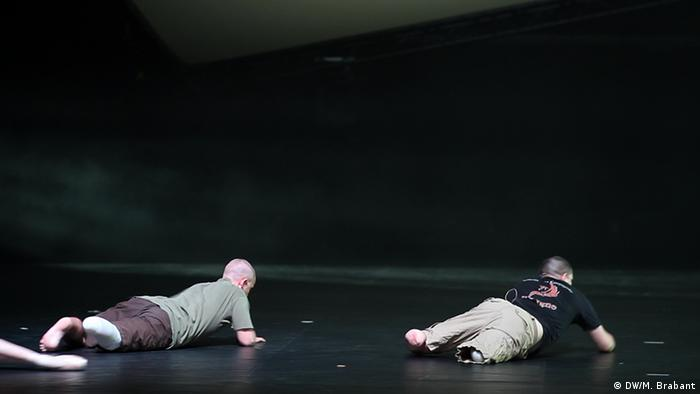 A photo showing two of the veterans in the ballet crawling off stage.