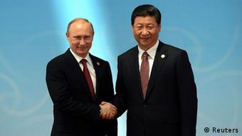 Russia's President Vladimir Putin (L) is greeted by his Chinese counterpart Xi Jinping (R) earlier this year in Shangai.
