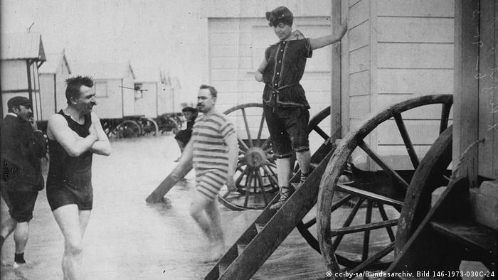 Badegäste im belgischen Ostende 1913 (Quelle: Wikipedia / http://commons.wikimedia.org/wiki/Swimsuit?uselang=de#mediaviewer/File:BathingMachinesOstendBain.jpg)