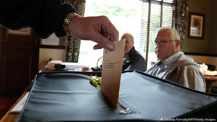 Vote being placed in a ballot box. LINDSEY PARNABY/AFP/Getty Images)